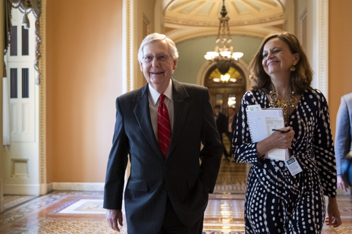 Senate Majority Leader Mitch McConnell, R-Ky., accompanied by Sharon Soderstrom, his chief of staff, smiles after a vote on a hard-won budget deal that would permit the government to resume borrowing to pay all of its obligations and would remove the prospect of a government shutdown in October, at the Capitol in Washington, Thursday, Aug. 1, 2019. (AP Photo/J. Scott Applewhite)