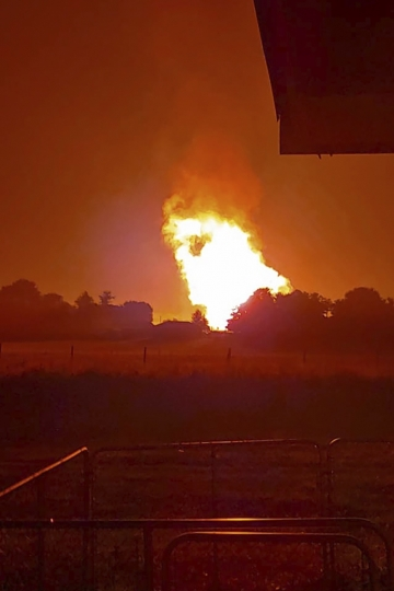 In this Thursday, Aug. 1, 2019 photo provided by Naomi Hayes, a fire burns after an explosion near Junction City, Ky. A regional gas pipeline ruptured early Thursday in Kentucky, causing a massive explosion that killed one person, hospitalized five others, destroyed railroad tracks and forced the evacuation of a nearby mobile home park, authorities said. (Naomi Hayes via AP)