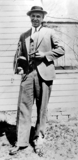 FILE - This is a 1934 file photo of desperado John Dillinger near Moore, Ind. The body of the 1930s gangster is set to be exhumed from an Indianapolis cemetery more than 85 years after he was killed by FBI agents. The Indiana State Department of Health approved a permit July 3, 2019, that Dillinger's nephew, Michael C. Thompson, sought to have the body exhumed from Crown Hill Cemetery and reinterred there. (AP Photo, File) .