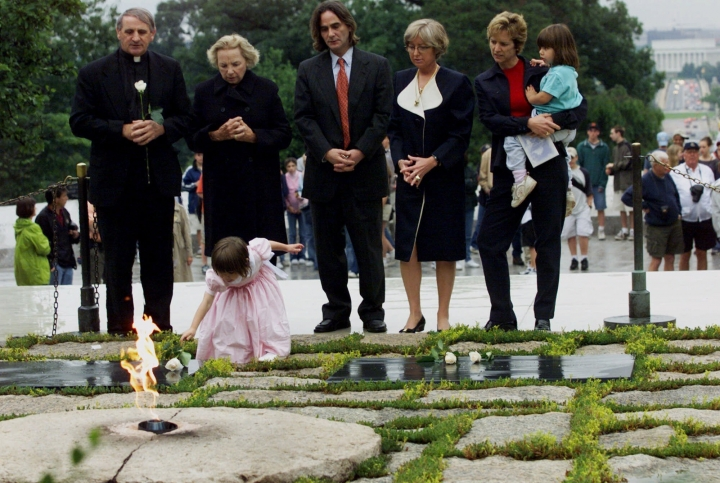 FILE - In this June 6, 2000 file photo, Robert F. Kennedy's granddaughter Saoirse Kennedy Hill places a white rose at the Eternal Flame, President John F. Kennedy's gravesite, at Arlington National Cemetery in Arlington, Va. Hill, has died at the age of 22. The Kennedy family released a statement on Thursday night, Aug. 1, 2019, following reports of a death at the family's compound in Hyannis Port, Massachusetts. Hill was the daughter of Robert and Ethel Kennedy's fifth child, Courtney, and Paul Michael Hill. (AP Photo/Hillery Smith Garrison, File)