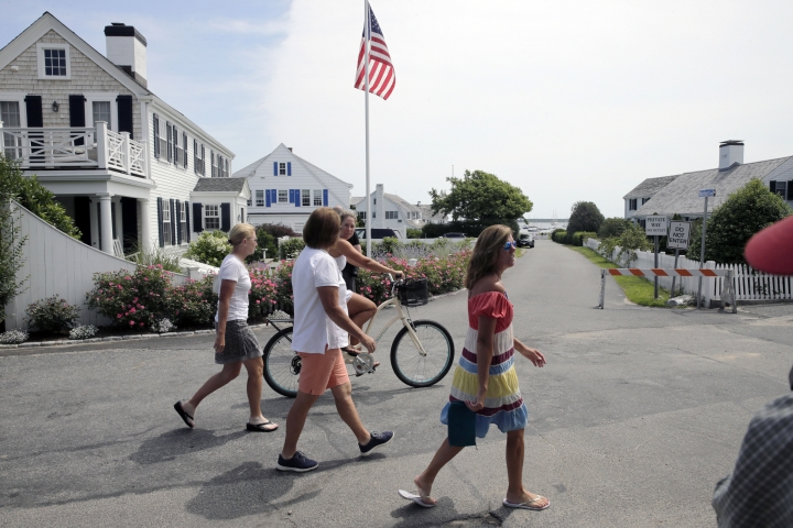 People walk past the street leading to the Kennedy compound on Friday, Aug. 2, 2019, in Hyannis Port, Mass. Saoirse Kennedy Hill, granddaughter of Ethel Kennedy and her late husband Robert F. Kennedy, died at the compound on Thursday. She was 22. (AP Photo/Charles Krupa)