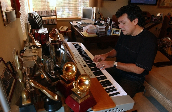 "FILE - This Jan. 6, 2005 file photo shows Latin songwriter Rudy Perez working on a composition at his home in Miami Beach, Fla. Perez has written a memoir titled ""The Latin Hitmaker: My Journey from Cuban Refugee to World-Renowned Record Producer and Songwriter."" (AP Photo/J. Pat Carter, File)"