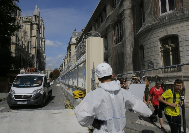 A worker dressed in a white overalls opens the gate on the fence that surround Notre-Dame Cathedral, in Paris, Thursday, Aug. 1, 2019, as the preliminary work begins to repair the fire damage. (AP Photo/Michel Euler)