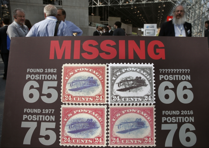 """FILE - In this June 2, 2016 file photo, a missing poster for the remaining """"Inverted Jenny,"""" one of four rare 1918 stamps featuring an airplane printed upside-down and stolen in 1955, is displayed at the World Stamp Show, in New York. Hopes by a small aviation museum in southwestern Iowa that a stamp in its possession was rare enough to parlay a potential fortune crashed Friday, Aug. 2, 2019, when experts told them it wasn't real, and likely not even worth the paper it was glued upon. The Iowa Aviation Museum in Greenfield, Iowa, had what it thought was an """"Inverted Jenny"""" stamp on display for some 20 years, but it wasn't authentic. (AP Photo/Kathy Willens, File)"""