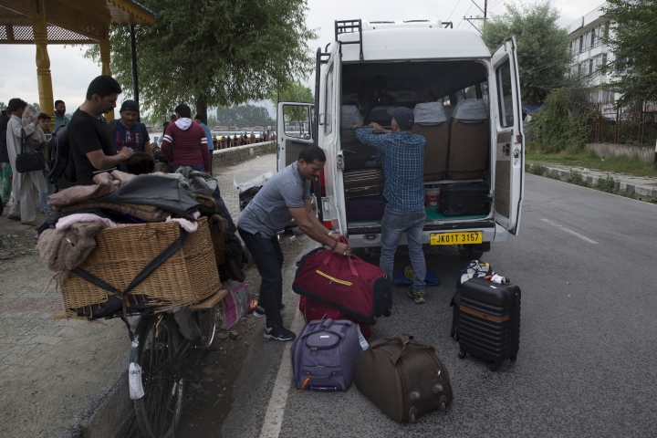 """Indian tourists load their luggage as they prepare to leave Srinagar, Indian controlled Kashmir, Saturday, Aug. 3, 2019. A government order in Indian-administered Kashmir on Friday asked tourists and Hindu pilgrims visiting a Himalayan cave shrine """"to curtail their stay"""" in the disputed territory, citing security concerns and intensifying tensions following India's announcement it was sending more troops to the region. (AP Photo/ Dar Yasin)"""