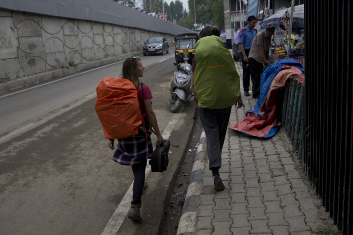 """Belgians tourists walks towards a taxi stand as they prepare to leave Srinagar, Indian controlled Kashmir, Saturday, Aug. 3, 2019. A government order in Indian-administered Kashmir on Friday asked tourists and Hindu pilgrims visiting a Himalayan cave shrine """"to curtail their stay"""" in the disputed territory, citing security concerns and intensifying tensions following India's announcement it was sending more troops to the region.(AP Photo/ Dar Yasin)"""