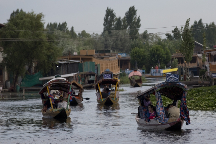 """Tourists in Shikaras, a traditional gondola, cross the Dal Lake as they prepare to leave Srinagar, Indian controlled Kashmir, Saturday, Aug. 3, 2019. A government order in Indian-administered Kashmir on Friday asked tourists and Hindu pilgrims visiting a Himalayan cave shrine """"to curtail their stay"""" in the disputed territory, citing security concerns and intensifying tensions following India's announcement it was sending more troops to the region. (AP Photo/ Dar Yasin)"""