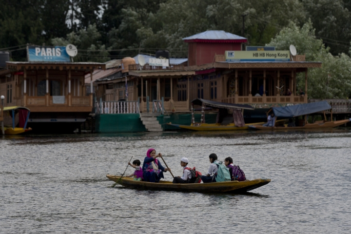 "A Kashmiri woman rows children to school on a shikara, a traditional gondola, on Dal Lake in Srinagar, Indian controlled Kashmir, Saturday, Aug. 3, 2019. A government order in Indian-administered Kashmir on Friday asked tourists and Hindu pilgrims visiting a Himalayan cave shrine ""to curtail their stay"" in the disputed territory, citing security concerns and intensifying tensions following India's announcement it was sending more troops to the region. (AP Photo/ Dar Yasin)"