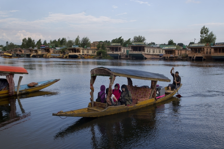 "Foreign tourists cross the Dal Lake on a Shikara as they prepare to leave Srinagar, Indian controlled Kashmir, Saturday, Aug. 3, 2019. A government order in Indian-administered Kashmir on Friday asked tourists and Hindu pilgrims visiting a Himalayan cave shrine ""to curtail their stay"" in the disputed territory, citing security concerns and intensifying tensions following India's announcement it was sending more troops to the region. (AP Photo/ Dar Yasin)"