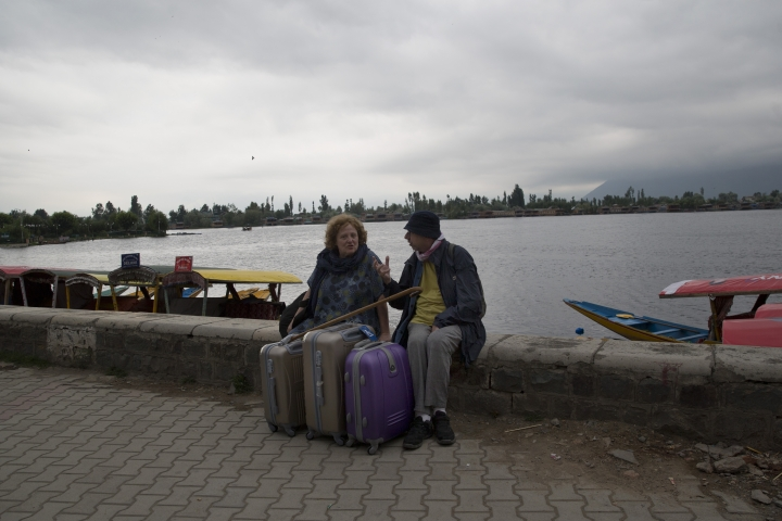"An Italian couple wait for their taxi as they prepare to leave Srinagar, Indian controlled Kashmir, Saturday, Aug. 3, 2019. A government order in Indian-administered Kashmir on Friday asked tourists and Hindu pilgrims visiting a Himalayan cave shrine ""to curtail their stay"" in the disputed territory, citing security concerns and intensifying tensions following India's announcement it was sending more troops to the region. (AP Photo/ Dar Yasin)"
