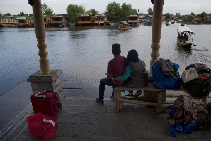 "An Indian couple waits for transport as they prepare to leave Srinagar, Indian controlled Kashmir, Saturday, Aug. 3, 2019. Thousands of Indian students and visitors were fleeing Indian-controlled Kashmir on Saturday after the government ordered tourists and Hindu pilgrims visiting a Himalayan cave shrine ""to curtail their stay"" in the disputed territory, citing security concerns. (AP Photo/ Dar Yasin)"
