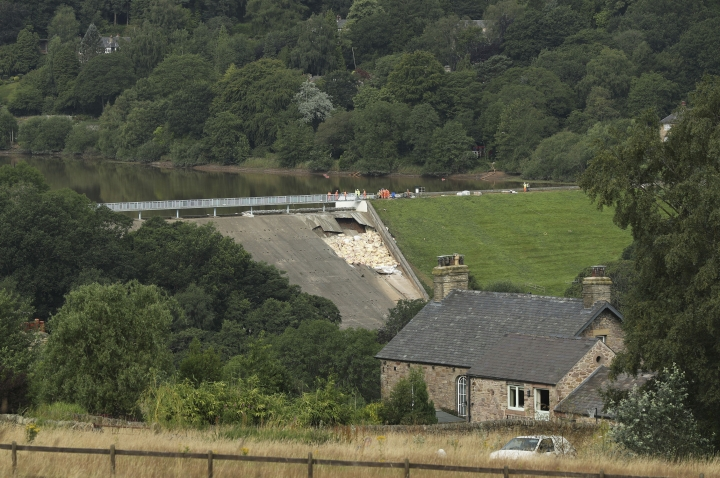 A view of the damaged Toddbrook Reservoir near the village of Whaley Bridge,in Derbyshire, England, Saturday, Aug. 3, 2019. Emergency workers are racing to lower water levels behind a damaged dam in northwest England as forecasters warn more bad weather is on the way. Pumps have reduced the water level in Toddbrook Reservoir by half a meter (20 inches) since Thursday, but authorities warn that pressure on the 180-year-old dam remains severe. (Yui Mok/PA via AP)