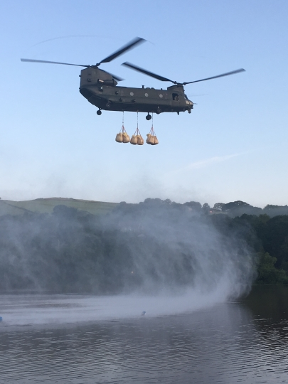 "In this image released by the Ministry of Defence, an RAF Chinook helicopter flies in sandbags to help repair the dam at Toddbrook reservoir near the village of Whaley Bridge in Derbyshire, England, Friday, Aug. 2, 2019. A British military helicopter dropped sandbags Friday to shore up a reservoir wall as emergency services worked frantically to prevent a rain-damaged dam from collapsing. Engineers said they remain ""very concerned"" about the integrity of the 19th-century Toddbrook Reservoir, which contains around 1.3 million metric tons (1.5 million (U.S tons) of water. (Gary Lane/Ministry of Defence via AP)"