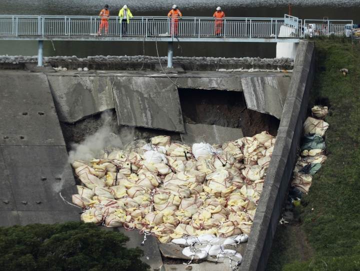 A bag of aggregate, a mixture of sand, gravel and stone, is thrown onto the damaged Toddbrook Reservoir near the village of Whaley Bridge,in Derbyshire, England, Saturday, Aug. 3, 2019. Emergency workers are racing to lower water levels behind a damaged dam in northwest England as forecasters warn more bad weather is on the way. Pumps have reduced the water level in Toddbrook Reservoir by half a meter (20 inches) since Thursday, but authorities warn that pressure on the 180-year-old dam remains severe. (Yui Mok/PA via AP)