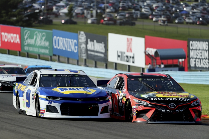Chase Elliott (9) holds off an attempted pass by Martin Truex, Jr., after a restart following a yellow caution flag during a NASCAR Cup Series auto race at Watkins Glen International, Sunday, Aug. 4, 2019, in Watkins Glen, N.Y. (AP Photo/John Munson)