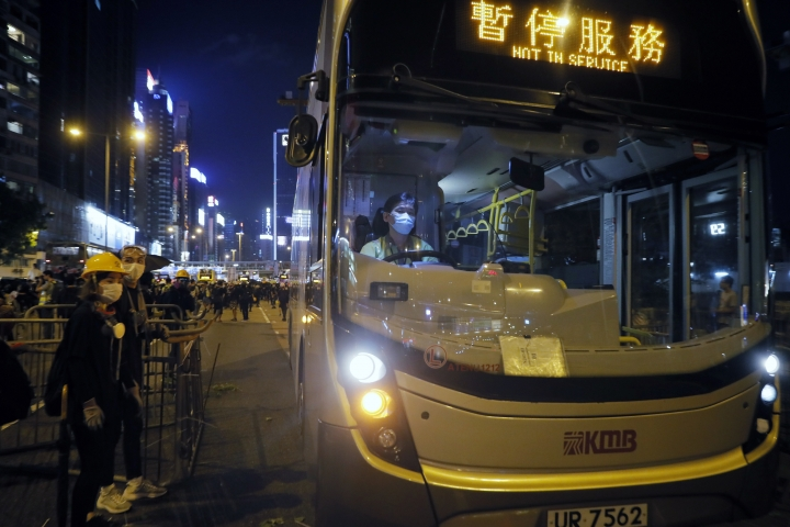 An off duty bus drives pass a barricades by protesters at Causeway Bay to hold the anti-extradition bill protest in Hong Kong, Sunday, Aug. 4, 2019. The first of two planned protests in Hong Kong on Sunday has kicked off from a public park just hours after police said they arrested more than 20 people for unlawful assembly and other offences during the previous night's demonstrations. (AP Photo/Kin Cheung)