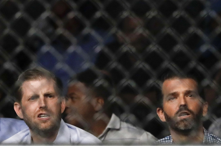 Eric Trump, left, and Donald Trump Jr. watch during the second round of a welterweight mixed martial arts bout between Robbie Lawler and Colby Covington at UFC Fight Night on Saturday, Aug. 3, 2019, in Newark, N.J. Covington won the bout. (AP Photo/Frank Franklin II)