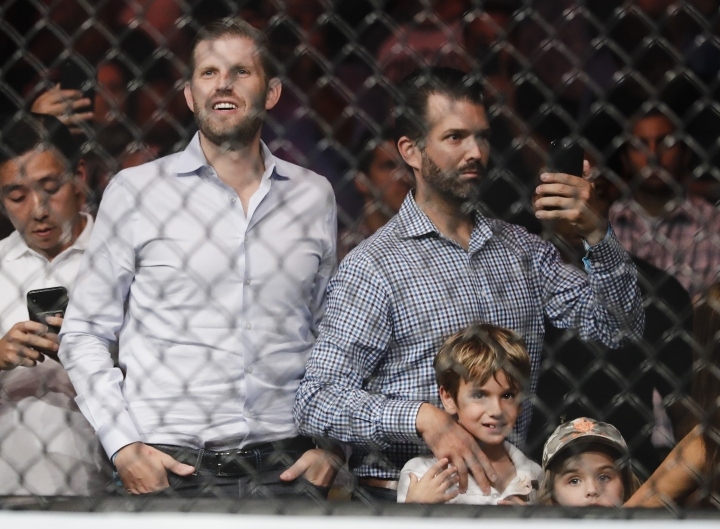 Eric Trump, left, and Donald Trump Jr., right, wait for the start of a welterweight mixed martial arts bout between Colby Covington and Robbie Lawler at UFC Fight Night Saturday, Aug. 3, 2019, in Newark, N.J. (AP Photo/Frank Franklin II)