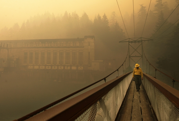 FILE - In this Aug. 26, 2015, file photo, Dennis Godfrey, with the Great Basin Incident Management Team 4, walks across a bridge from the Gorge Powerhouse through heavy smoke from a nearby wildfire near Newhalem, Wash. The region, famous for its rainfall, has long escaped major burns even as global warming has driven an increase in both the size and number of wildfires elsewhere in the American West. But according to experts, previously too-wet-to-burn parts of the Pacific Northwest now face an increasing risk of significant wildfires because of climate change. (Mark Mulligan/The Herald via AP, File)