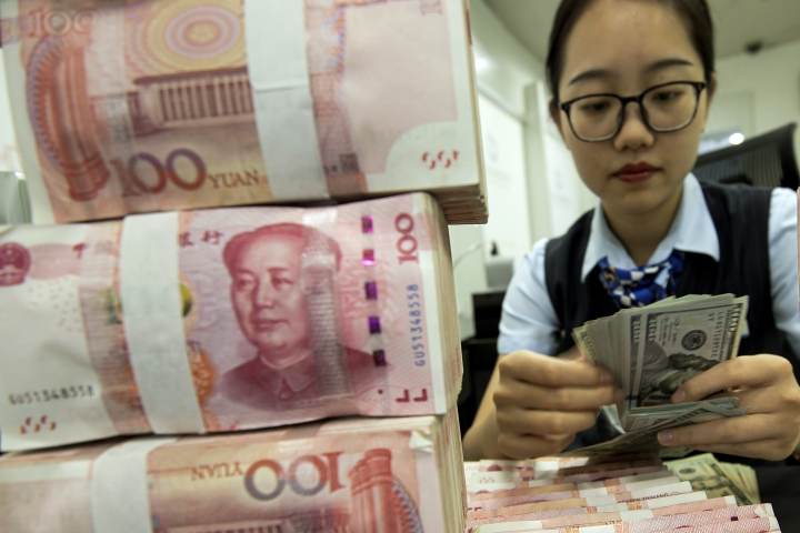 A bank employee counts U.S. dollar banknotes next to stack of 100 Chinese yuan notes at a bank outlet in Hai'an in eastern China's Jiangsu province, Tuesday, Aug. 6, 2019. China's yuan fell further Tuesday against the U.S. dollar, fueling fears about increasing global damage from Beijing's trade war with President Donald Trump. (Chinatopix via AP)