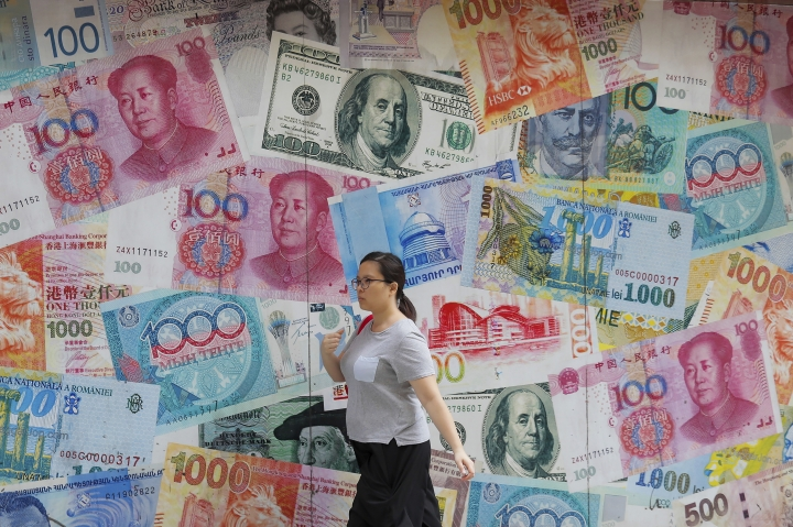 A woman walks by a money exchange shop decorated with different countries currency banknotes at Central, a business district in Hong Kong, Tuesday, Aug. 6, 2019. China's yuan fell further Tuesday against the U.S. dollar, fueling fears about increasing global damage from Beijing's trade war with President Donald Trump. (AP Photo/Kin Cheung)