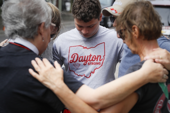 Mourners gather and share a pray near a makeshift memorial Tuesday, Aug. 6, 2019, for the slain and injured in the Oregon District after a mass shooting that occurred early Sunday morning, in Dayton. (AP Photo/John Minchillo)