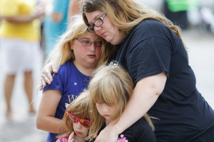 Mourners embrace after bringing flowers to a makeshift memorial Tuesday, Aug. 6, 2019, for the slain and injured in the Oregon District after a mass shooting that occurred early Sunday morning, in Dayton, Ohio. (AP Photo/John Minchillo)