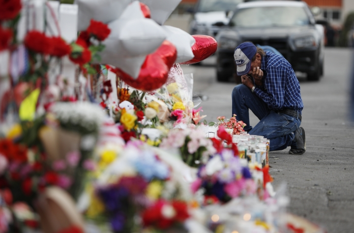 A man cries beside a cross at a makeshift memorial near the scene of a mass shooting at a shopping complex Tuesday, Aug. 6, 2019, in El Paso, Texas. The border city jolted by a weekend massacre at a Walmart absorbed more grief Monday as the death toll climbed and prepared for a visit from President Donald Trump over anger from El Paso residents and local Democratic leaders who say he isn't welcome and should stay away. (AP Photo/John Locher)