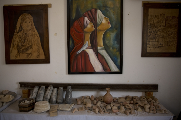 In this July 17, 2019 photo, paintings decorate the wall over ancient artifacts displayed inside Al-Qarara private museum in town of Khan Younis, Southern Gaza Strip. Gaza was a major trade route between Egypt and the Levant for thousands of years, but decades of uprisings, war and political turmoil have inflicted a heavy toll on its rich archaeological heritage, exposing it to looting and destruction. Neglect by Hamas authorities and a blockade imposed by Israel and Egypt have hindered efforts to preserve and protect antiquities, leaving much of the work to private collectors. (AP Photo/Khalil Hamra)