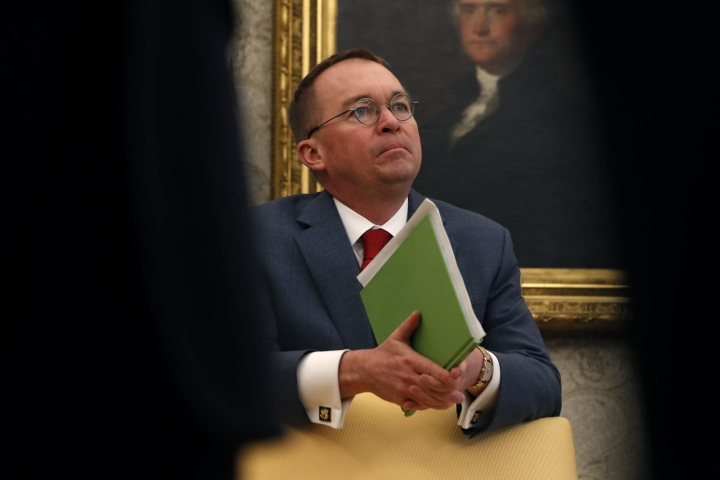 """FILE - In this Jan. 31, 2019, file photo, acting White House chief of staff Mick Mulvaney listens as President Donald Trump speaks during a meeting with American manufacturers in the Oval Office of the White House in Washington. A federal employees union says recent comments by acting White House chief of staff Mick Mulvaney confirm the Trump administration's """"grand strategy"""" to cut the federal workforce by relocating agency offices out of Washington. (AP Photo/Jacquelyn Martin, File)"""