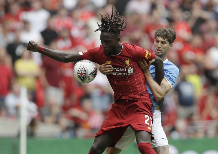 Liverpool's Divock Origi, left, challenges for the ball with Manchester City's John Stones during the English Community Shield soccer match between Liverpool and Manchester City at Wembley stadium in London, Sunday, Aug. 4, 2019. (AP Photo/Kirsty Wigglesworth)