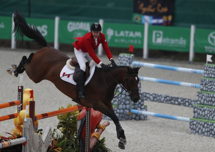 Mario Deslauriers competes for Canada on his horse Amsterdam 27 in the first classification round of individual and team equestrian jumping at the Pan American Games in Lima, Peru, Tuesday, Aug. 6, 2019. His daughter Lucy Deslauriers, who he helps coach, was competing against him in the same event for the United States. (AP Photo/Rebecca Blackwell)