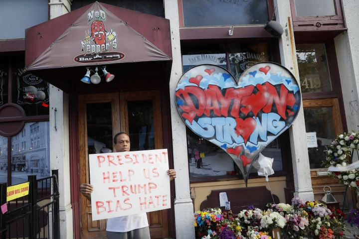 Damon Smith presents a message to President Donald Trump beside a makeshift memorial for the slain and injured victims of a mass shooting that occurred in the Oregon District early Sunday morning, Wednesday, Aug. 7, 2019, in Dayton, Ohio. Twenty-four-year-old Connor Betts opened fire in Dayton early Sunday, killing several people including his sister, before officers fatally shot him. (AP Photo/John Minchillo)