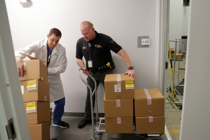 Bo Druilhet, left, director of cultivation for GB Sciences Louisiana, stacks boxes of the first ever shipment of medical marijuana in the state of Louisiana, at their facility in Baton Rouge, La., Tuesday, Aug. 6, 2019. At right is an armed private security agent, who was working with the East Baton Rouge Sheriff deputies protecting the transport. (AP Photo/Gerald Herbert)
