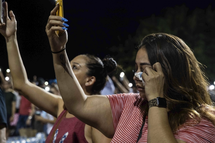 Amanda Beltran holds her cell phone flashlights up as she wipes her tears away during a vigil Sunday, Aug. 4, 2019, at Ponder Park in honor of the victims of the mass shooting that occurred in Walmart on Saturday, Aug. 3, 2019, in El Paso, Texas. (Lola Gomez/Austin American-Statesman via AP)