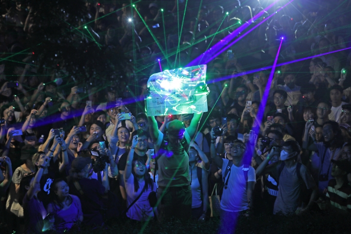 """Protesters focus the laser pointers to a newspaper as they try to burn it, during a rally to demonstrate against the arrests of people caught in possession of laser pointers that police classified as offensive weapons because of their ability to harm the eyes in Hong Kong, Wednesday, Aug. 7, 2019. Hong Kong is facing its """"most severe situation"""" since its handover from British rule in 1997 following weeks of demonstrations and the central government is considering what measures to take next, the head of Beijing's Cabinet office responsible for the territory said Wednesday. (AP Photo/Kin Cheung)"""