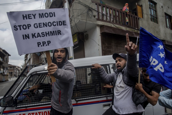 FILE - In this May 19, 2018, file photo, supporters of separatist People's Political Party (PPP) leader Hilal Ahmad War hold banners and shout slogans during a protest against the visit of Indian Prime Minister Narendra Modi in Srinagar, Indian controlled Kashmir. Modi's vision of a Hindu India took a leap forward with his government's decision in August, 2019, to subsume Kashmir into the federal government by eliminating its special status and allowing anyone to buy property and move into the state, raising fears among residents that they will lose their distinct identity. Modi's home minister, Amit Shah, considered the architect of the Hindu nationalist-led government's aggressive agenda to convert India from a secular, multicultural democracy into a distinctly Hindu, culturally and politically homogenous state, sold the new policy on Kashmir to parliament by equating it with Pakistan, India's staunch foe. (AP Photo/Dar Yasin, File)