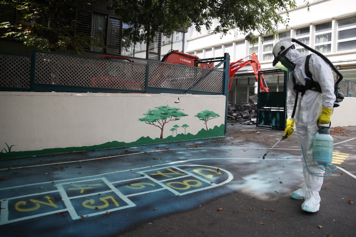 A worker sprays an adhesive product on the ground to gather up the lead particles in the school yard of Saint Benoit primary school in Paris, France, Thursday, Aug. 8, 2019. Workers have started decontaminating some Paris schools tested with unsafe levels of lead following the blaze at the Notre Dame Cathedral, as part of efforts to protect children from risks of lead poisoning. (AP Photo/Francois Mori)