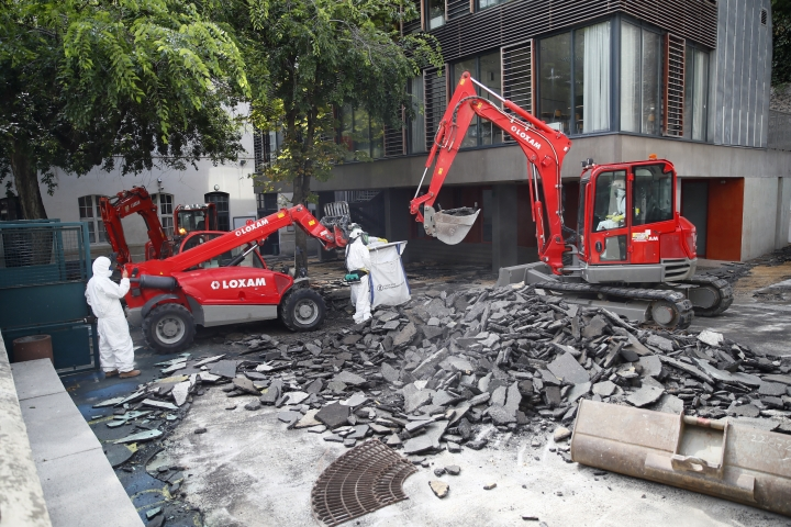 Workers direct a mechanical shovel grabbing pieces of destroyed surfacing to gather up the lead particles in the school yard of Saint Benoit primary school in Paris, France, Thursday, Aug. 8, 2019. Workers have started decontaminating some Paris schools tested with unsafe levels of lead following the blaze at the Notre Dame Cathedral, as part of efforts to protect children from risks of lead poisoning. (AP Photo/Francois Mori)