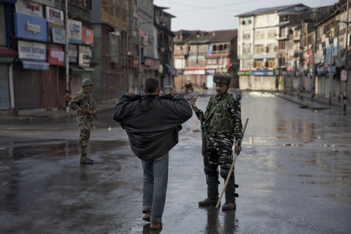 An Indian Paramilitary soldier orders a Kashmiri to lift his robe before frisking him during curfew in Srinagar, Indian controlled Kashmir, Thursday, Aug. 8, 2019. The lives of millions in India's only Muslim-majority region have been upended since the latest, and most serious, crackdown followed a decision by New Delhi to revoke the special status of Jammu and Kashmir and downgrade the Himalayan region from statehood to a territory. Kashmir is claimed in full by both India and Pakistan, and rebels have been fighting Indian rule in the portion it administers for decades. (AP Photo/Dar Yasin)