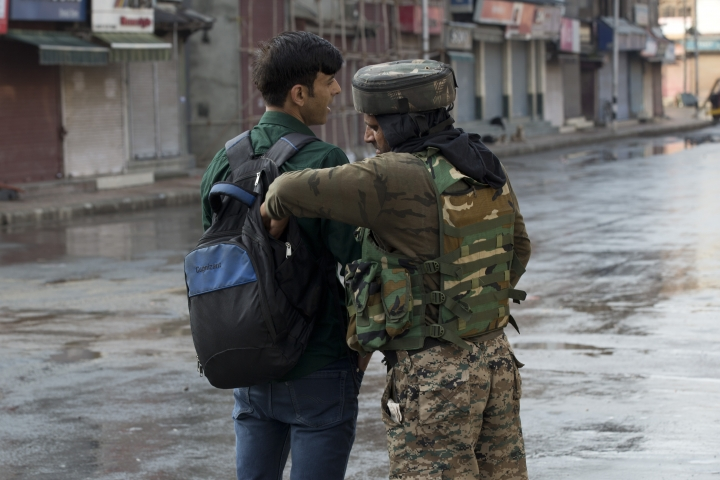 An Indian Paramilitary soldier checks the bag of a Kashmiri man during curfew in Srinagar, Indian controlled Kashmir, Thursday, Aug. 8, 2019. The lives of millions in India's only Muslim-majority region have been upended since the latest, and most serious, crackdown followed a decision by New Delhi to revoke the special status of Jammu and Kashmir and downgrade the Himalayan region from statehood to a territory. Kashmir is claimed in full by both India and Pakistan, and rebels have been fighting Indian rule in the portion it administers for decades. (AP Photo/Dar Yasin)