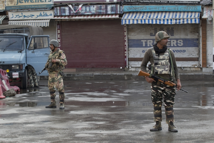 Indian Paramilitary soldiers stand guard on a deserted street during curfew in Srinagar, Indian controlled Kashmir, Thursday, Aug. 8, 2019. The lives of millions in India's only Muslim-majority region have been upended since the latest, and most serious, crackdown followed a decision by New Delhi to revoke the special status of Jammu and Kashmir and downgrade the Himalayan region from statehood to a territory. Kashmir is claimed in full by both India and Pakistan, and rebels have been fighting Indian rule in the portion it administers for decades. (AP Photo/Dar Yasin)