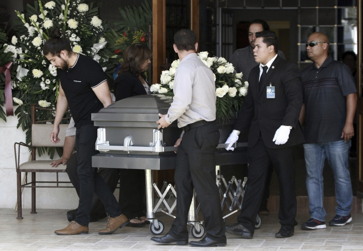 The casket with the body of elementary school principal Elsa Mendoza, of one of the 22 people killed in a shooting at a Walmart in El Paso, is rolled in to her funeral, in Ciudad Juarez, Mexico, Thursday, Aug. 8, 2019. Mexican officials have said eight of the people killed in Saturday's attack were Mexican nationals. (AP Photo/Christian Chavez)