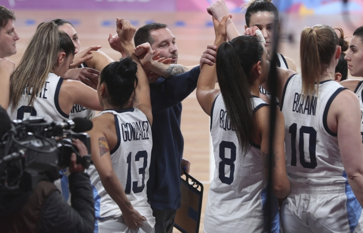 ADDS REASON WHY ARGENTINA IS OUT OF THE MEDAL ROUND - Argentina's coach Leonardo Costa, center, comforts his players during the women's basketball match against the Virgin Islands at the Pan American Games in Lima, Peru, Thursday, Aug. 8, 2019. Argentina's women's basketball team had to forfeit its match against Colombia at the Pan American Games on Wednesday for wearing the wrong uniform color. Argentina won today's match against the Virgin Islands but is out of the medal rounds because of the uniform blunder. (AP Photo/Martin Mejia)