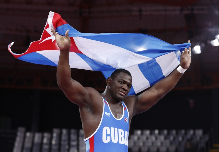 Cuba's Mijain Lopez runs with his nation's flag after defeating Venezuela's Moises Perez to win gold in their men's 130kg Greco-Roman wrestling final bout at the Pan American Games in Lima, Peru, Thursday, Aug. 8, 2019. (AP Photo/Rebecca Blackwell)