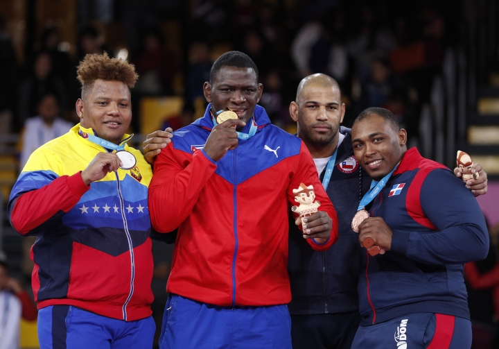 From left, silver medalist Venezuela's Moises Perez, gold medalist Cuba's Mijain Lopez, and bronze medalists Yasmani Acosta of Chile and Leo Santana of the Dominican Reublic pose with their medals in the men's 130kg Greco-Roman wrestling at the Pan American Games in Lima, Peru, Thursday, Aug. 8, 2019. (AP Photo/Rebecca Blackwell)