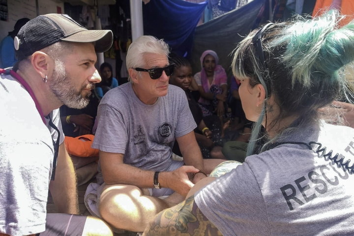Actor Richard Gere, center, talks with staff members of the Open Arms Spanish humanitarian boat as it cruises in the Mediterranean Sea, Friday, Aug. 9, 2019. Open Arms has been carrying 121 migrants for a week in the central Mediterranean awaiting a safe port to dock, after it was denied entry by Italy and Malta. (AP Photo/Valerio Nicolosi)