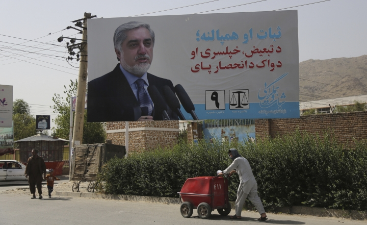 An Afghan ice-cream vendor walk past an election hoarding of a presidential candidate Abdullah Abdullah in Kabul,Afghanistan Friday, Aug. 9, 2019. Afghanistan faces a presidential election next month but few believe the vote will take place as the United States and the Taliban inch closer to a deal that could end the nearly 18-year war but bring uncertainty about almost everything else. (AP Photo/Nishanuddin Khan)