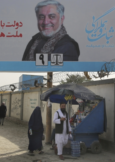 Afghans walk past an election hoarding of a presidential candidate Abdullah Abdullah in Kabul,Afghanistan Friday, Aug. 9, 2019.Afghanistan faces a presidential election next month but few believe the vote will take place as the United States and the Taliban inch closer to a deal that could end the nearly 18-year war but bring uncertainty about almost everything else.(AP Photo/Nishanuddin Khan)