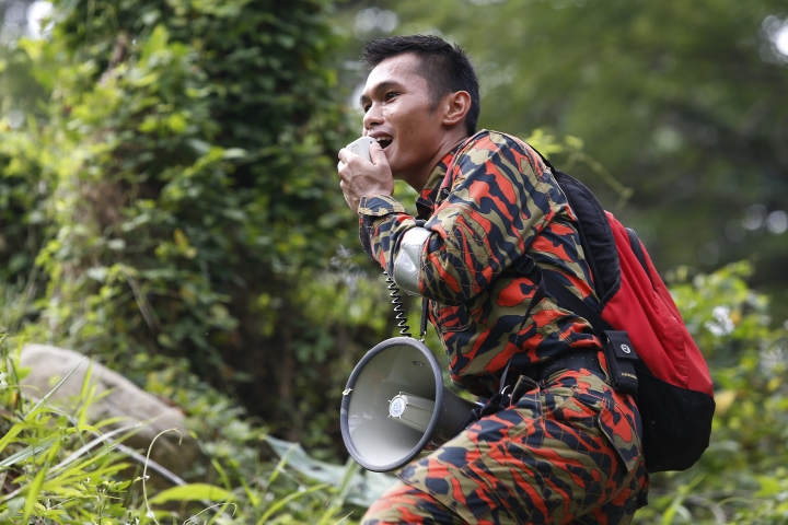 A member of a rescue team uses a loudspeaker as he conducts a search and rescue operation for a missing British girl at a forest in Seremban, Negeri Sembilan, Malaysia, Friday, Aug. 9, 2019. Police in Malaysia said on Thursday that they are using voice recordings conducted with the family of the 15-year old missing girl from London, in order to find her. (AP Photo/Lai Seng Sin)